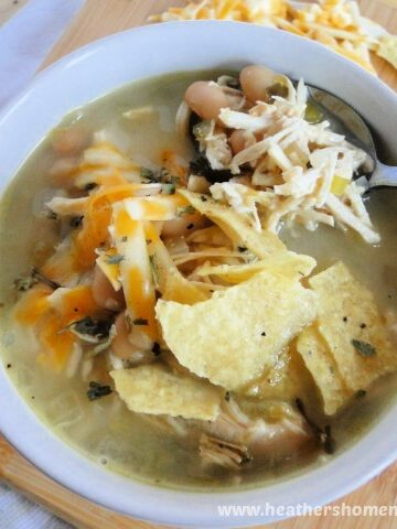 Spoonful of crock pot white chicken chili in white bowl with shredded cheese and tortilla chips on top.