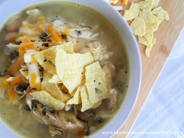 Crock Pot White Chicken Chili with shredded cheese and tortilla chips on top.