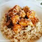 Side view of instant pot honey garlic chicken over rice with sesame seeds on top.