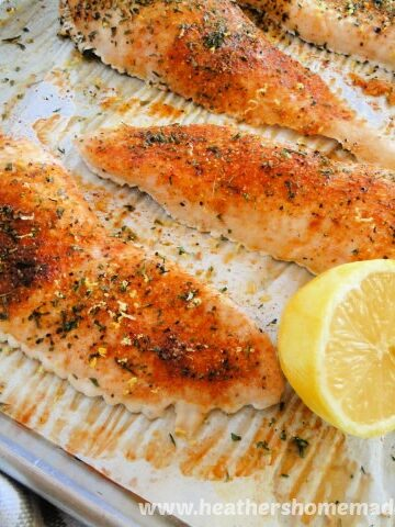 Simple Roasted Chicken Breasts on sheet pan with lemon half.