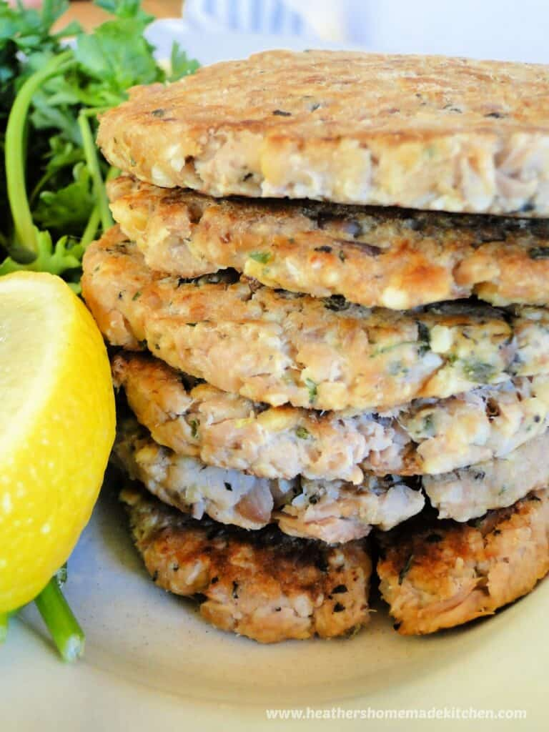 Stack of healthy basil tuna cakes with a lemon wedge.