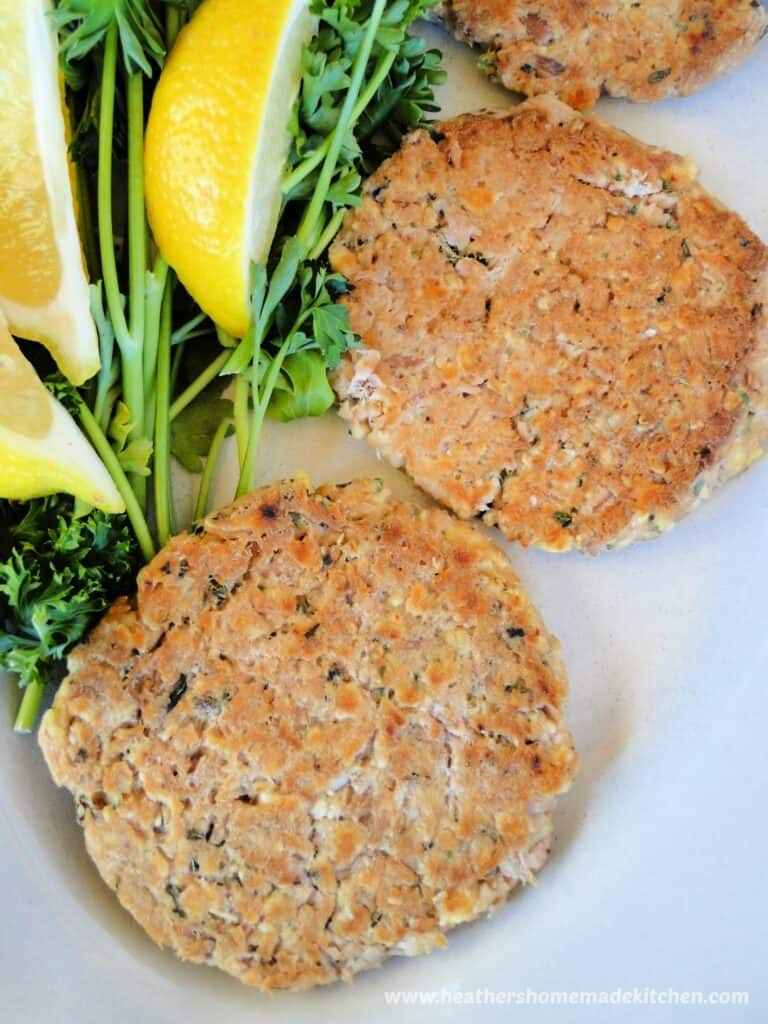 Healthy basil tuna cakes on white plate with lemon wedges.