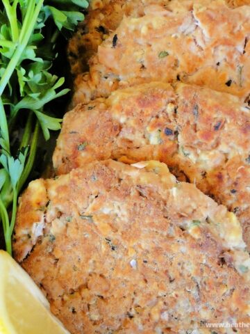 Healthy basil tuna cakes spread on white platter with parsley and lemon wedges.
