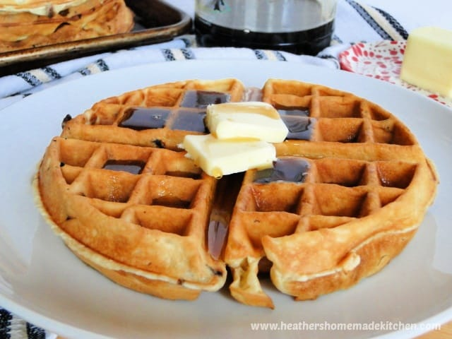 Easy homemade Chocolate chip waffle with pats of butter and syrup on white round plate in front on bottle of syrup.