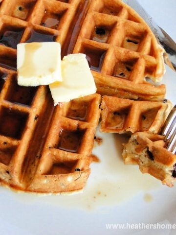 Easy homemade Chocolate Chip Waffles on white round plate with pats of butter, maple syrup and bite taken out with fork and knife.