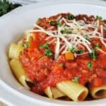 Crock pot beef bolognese made in slow cooker over pasta topped with shredded parmesan cheese and parsley in white bowl.