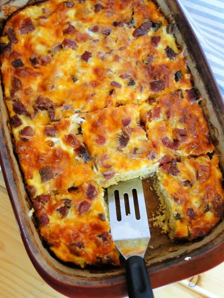 Golden brown best ever egg bake sliced in casserole dish with spatula.