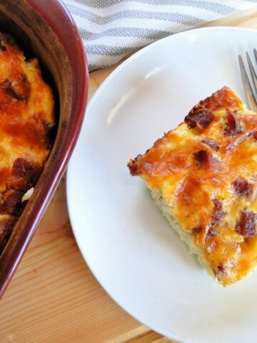 Best ever egg bake slice on white round plate with fork next to casserole dish of egg bake.
