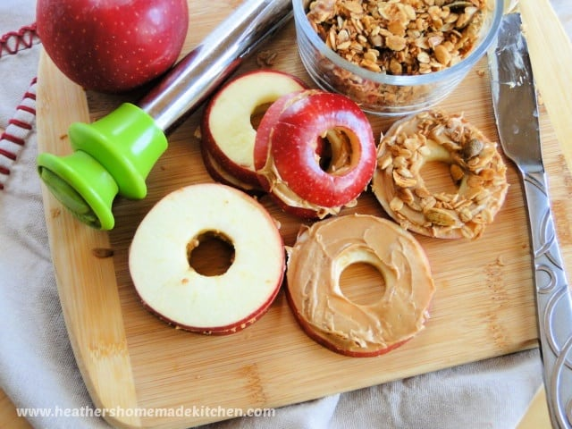Top view of Peanut Butter Apple Sandwiches with an apple with peanut butter smear on board with an apple cored and bowl of granola.