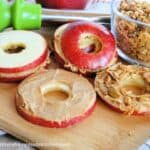 Peanut Butter Apple sandwiches with granola on board with apple slice and peanut butter and bowl of granola.