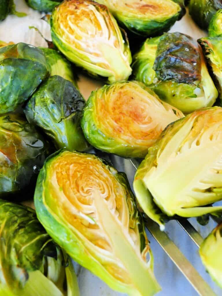 Close up of roasted brussels sprouts on spatula and sheet pan.