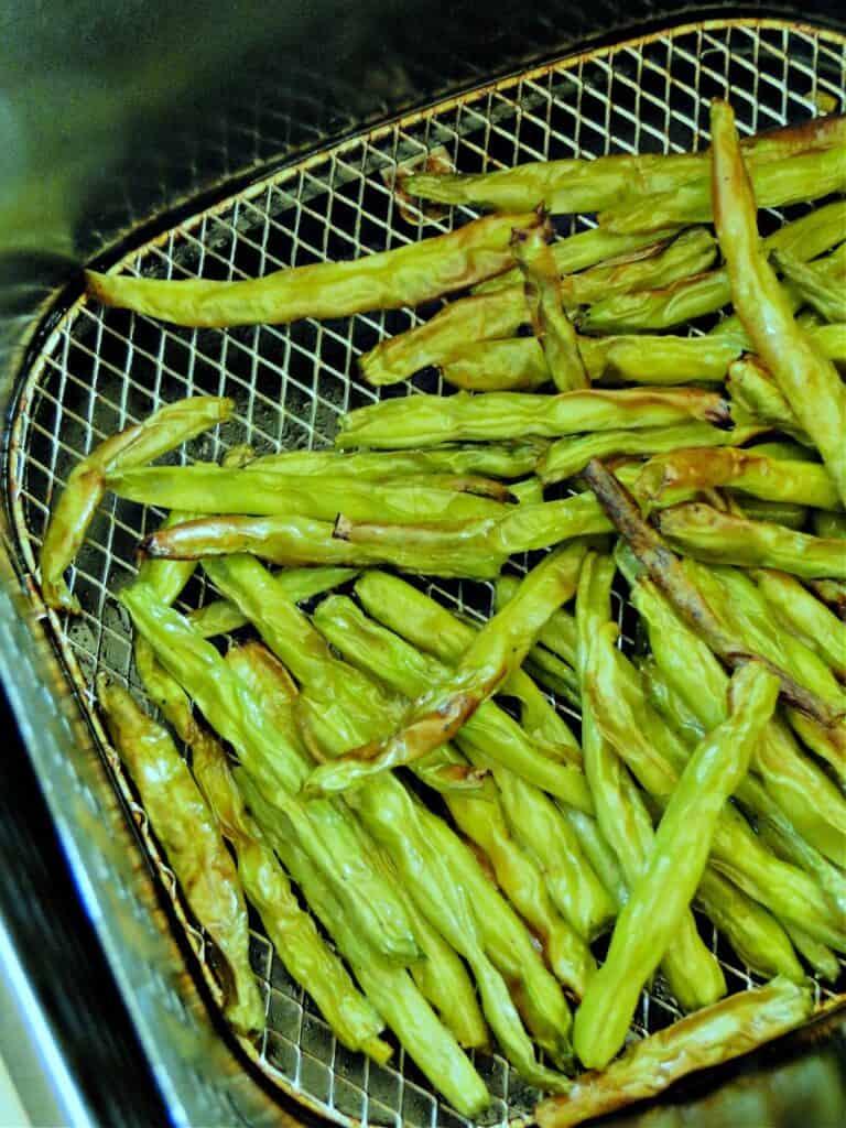 Top view of air fryer green beans in air fryer basket.