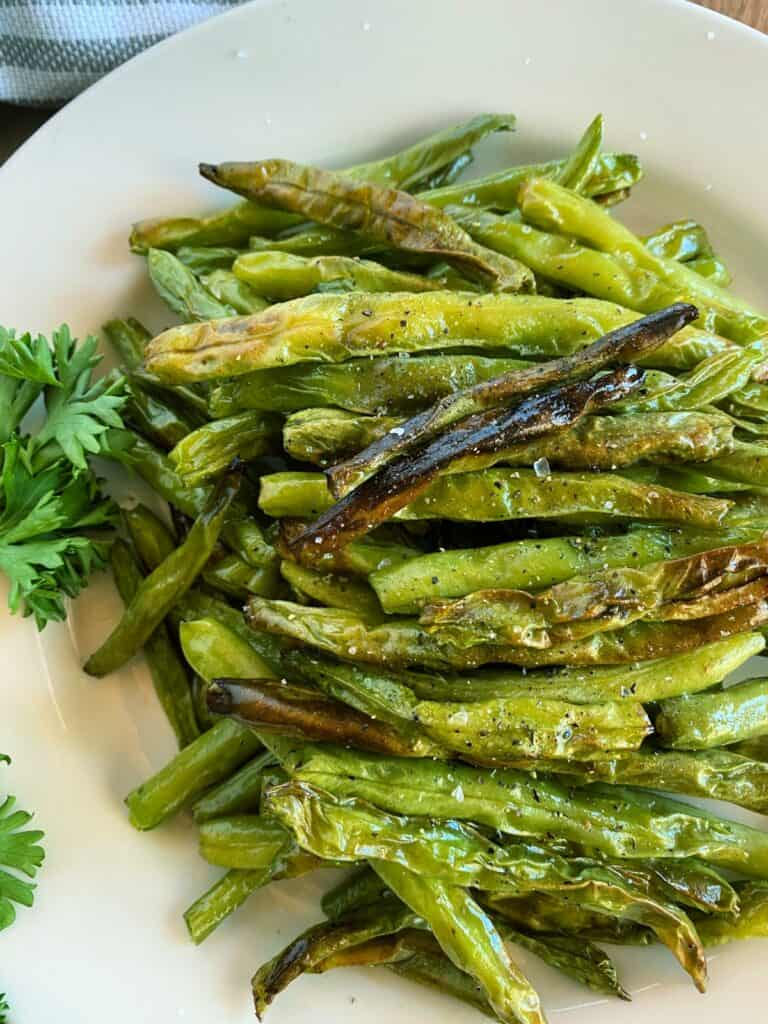 Pile of air fryer green beans sprinkled with salt and pepper on a white round platter.
