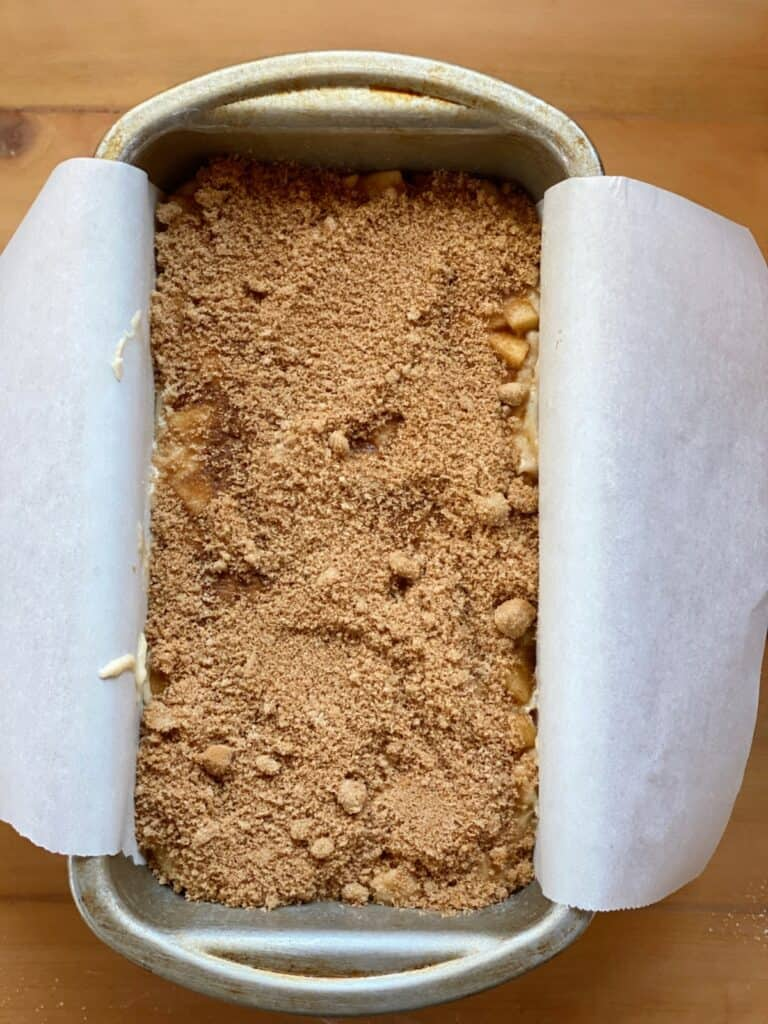 Apple fritter loaf topped with cinnamon sugar mix in 9x5 loaf pan.