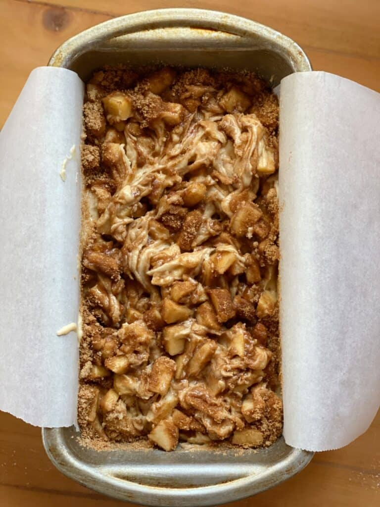 Apple fritter loaf with cinnamon sugar topping swirled in batter in 9x5 loaf pan.