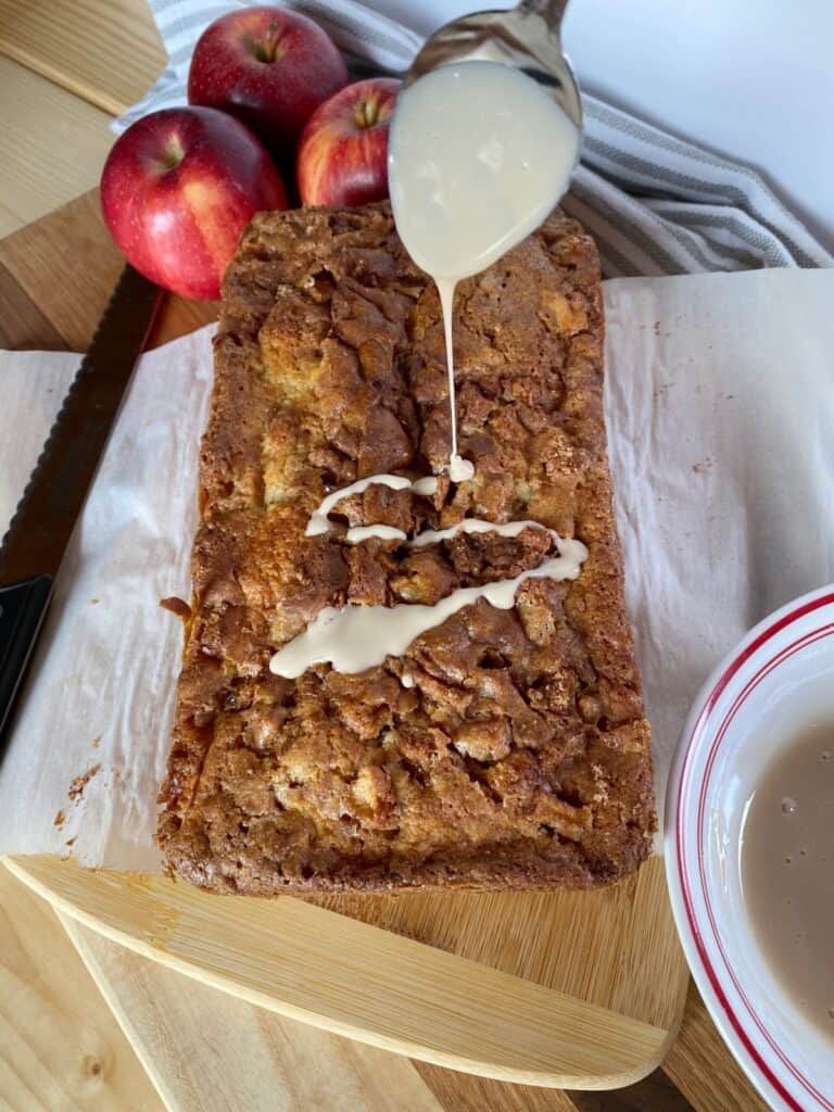 Apple fritter loaf being drizzled with maple glaze.