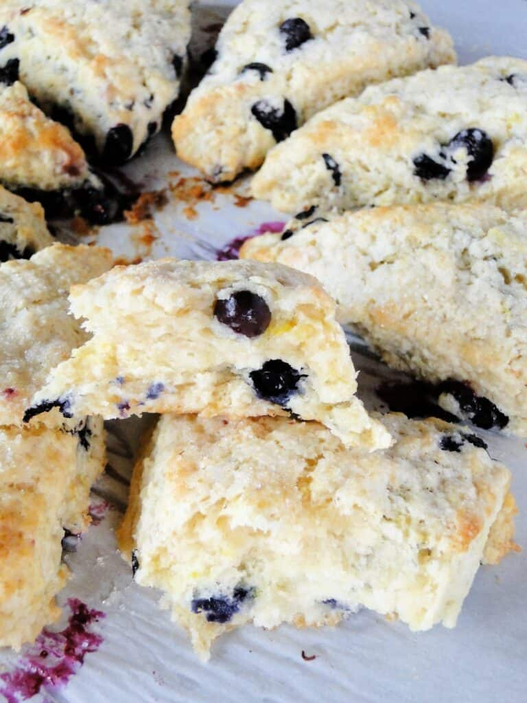 Blueberry scones on sheet pan with close up view of one scone broken in half showing flaking inside.