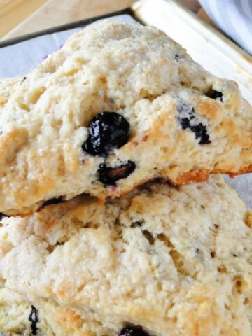 Side view of blueberry scones with golden edges stacked on sheet pan.