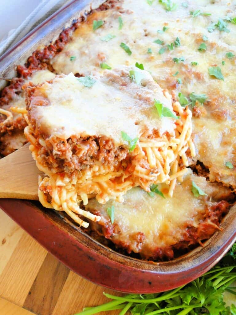 Casserole dish of Cheesy Spaghetti Bake with a portion scooped on bamboo spatula.