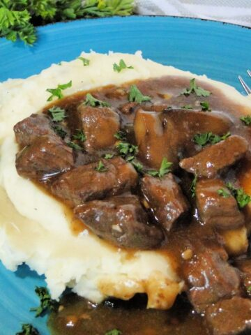 Instant pot beef tips and gravy over mashed potatoes with parsley garnish on blue round plate.