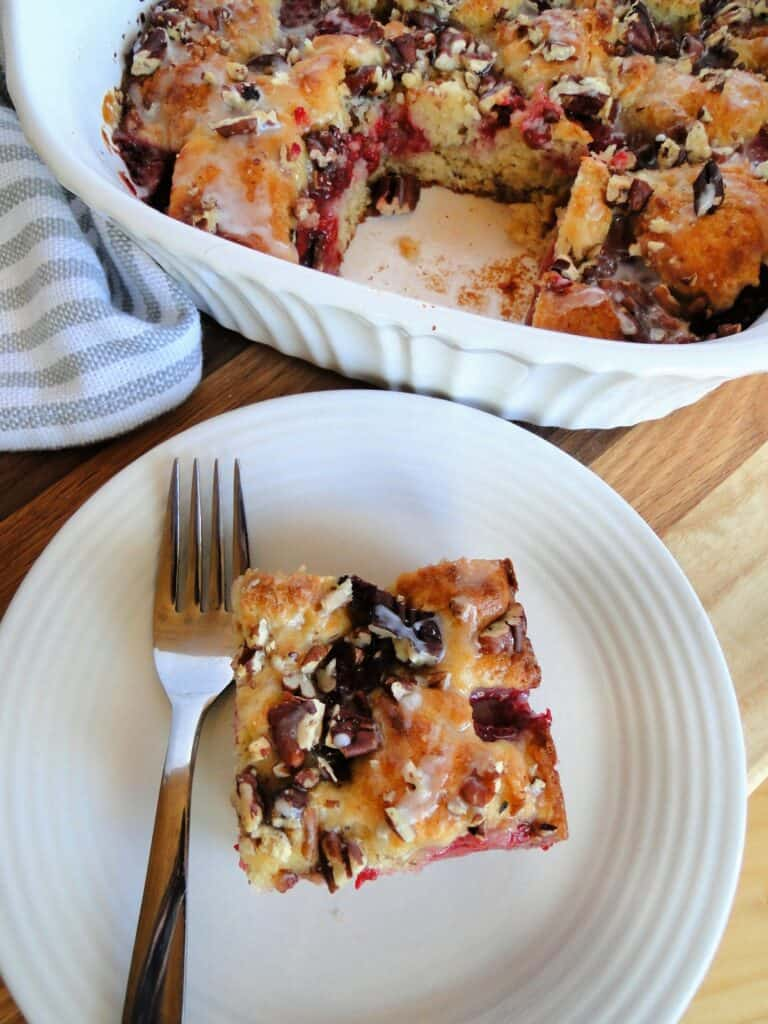 Top view of Raspberry Coffee cake slice on white round plate with fork.