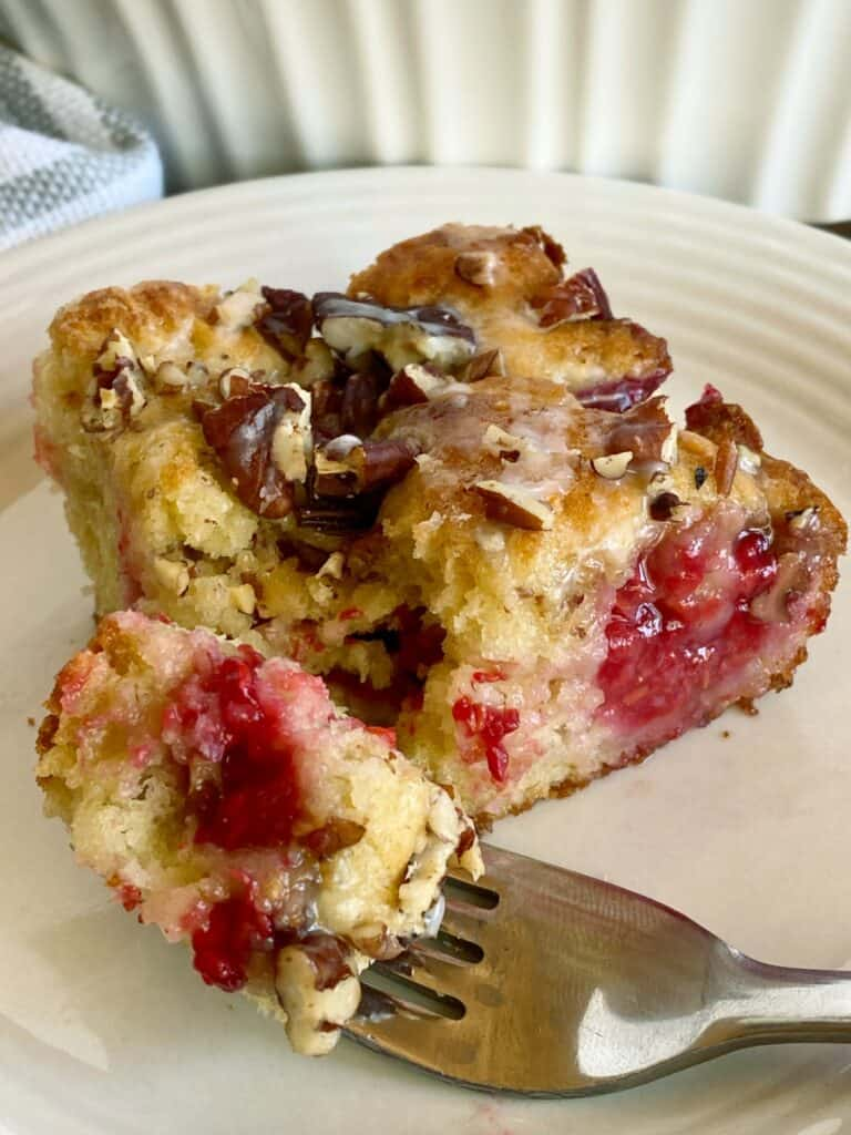 Slice of Raspberry coffee cake on white round plate with bite on fork.