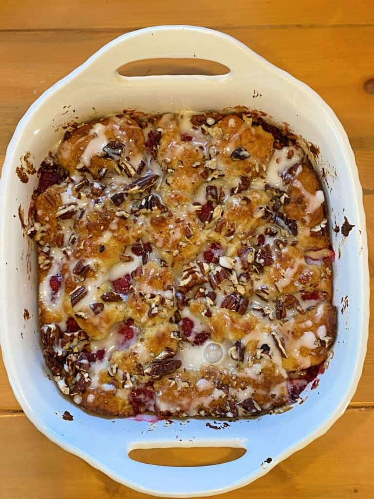 Baked raspberry coffee cake with icing drizzled on top.