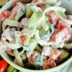 Creamy tomato cucumber salad with sliced onions in bowl.