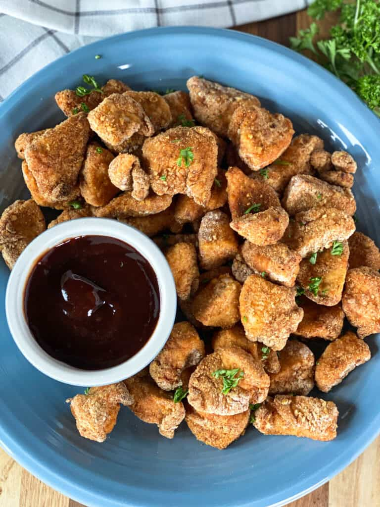Top view of air fryer chicken nuggets on blue plate with BBQ sauce for dipping.