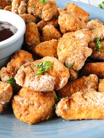 Air fryer chicken nuggets on blue plate with BBQ sauce for dipping.