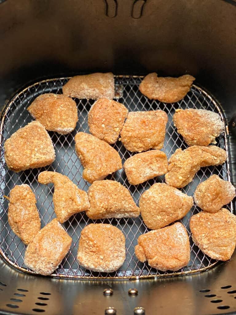 Breaded chicken bites in air fryer basket sprayed with olive oil.