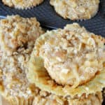 Apple pie muffins with paper lining pulled off one muffin.