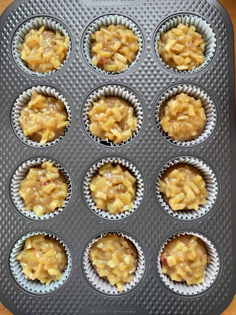 Muffin batter in muffin pan topped with apple pie filling.