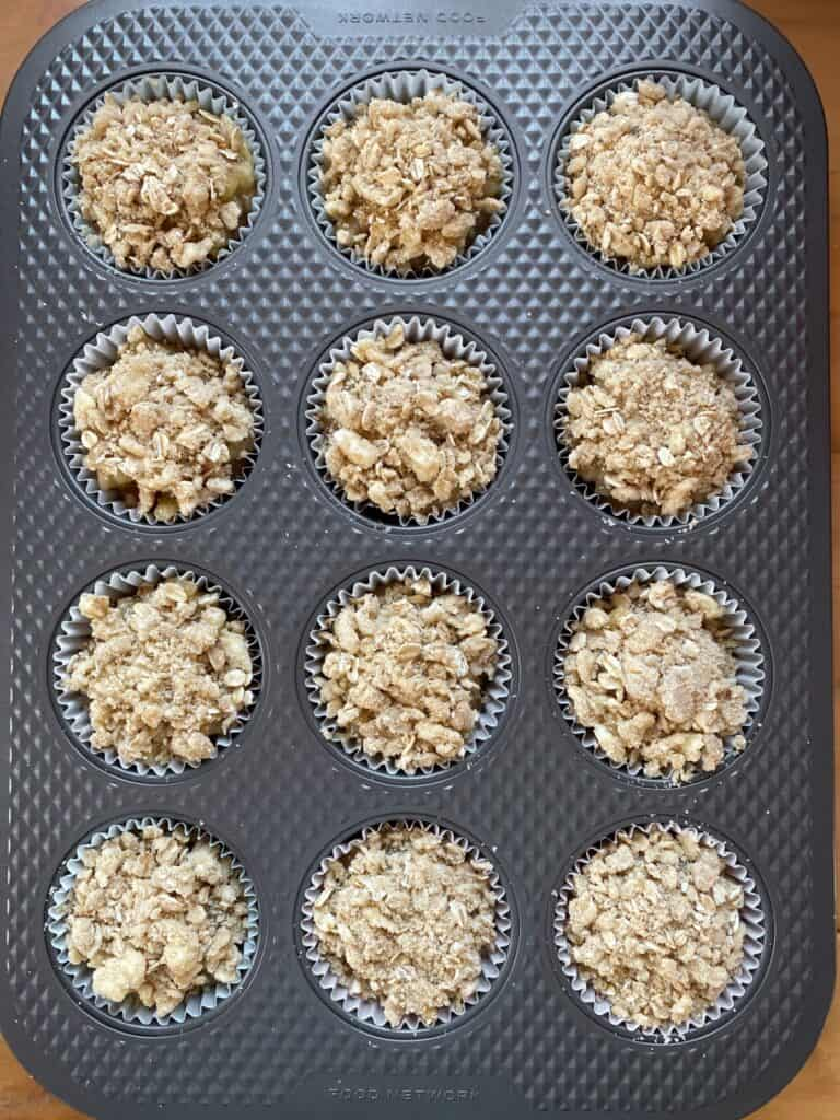 Muffin batter topped with apple pie filling and streusel in muffin pan.