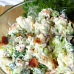 Broccoli and Cauliflower salad in glass bowl with scoop on wooden spoon.