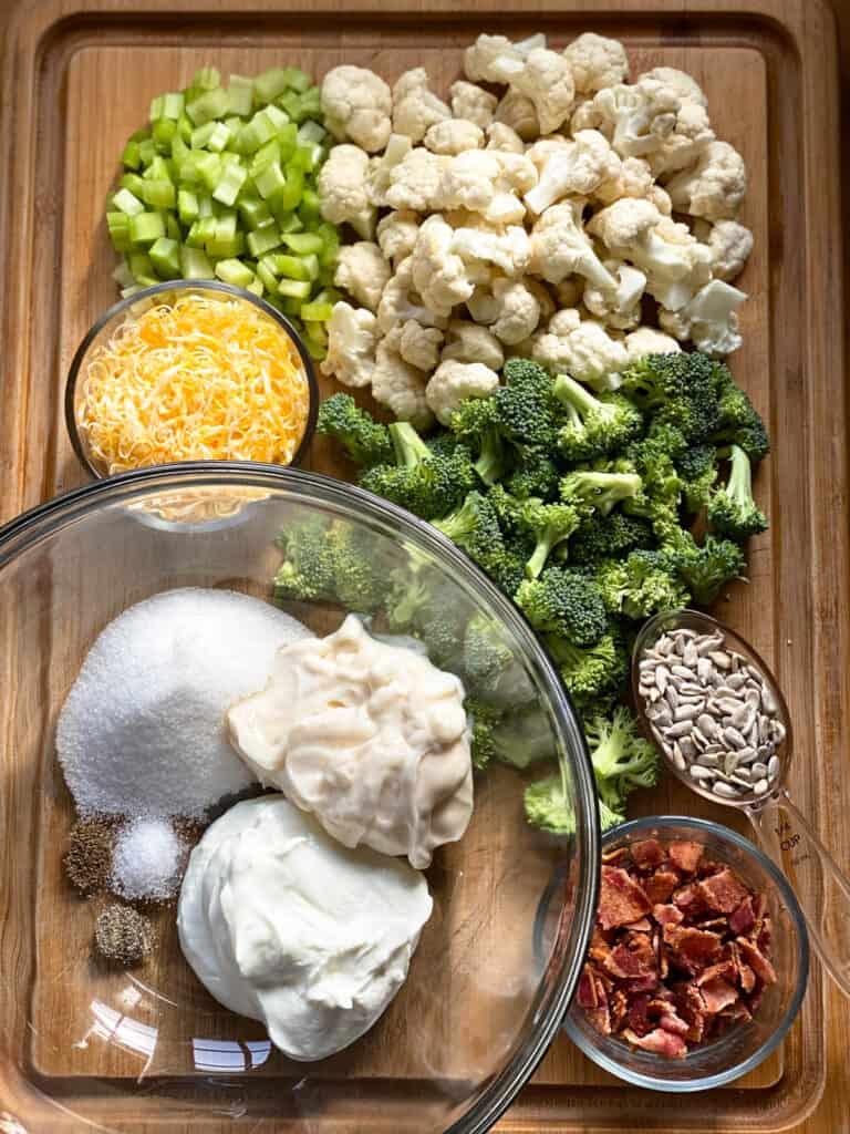 Broccoli and cauliflower salad ingredients on board.