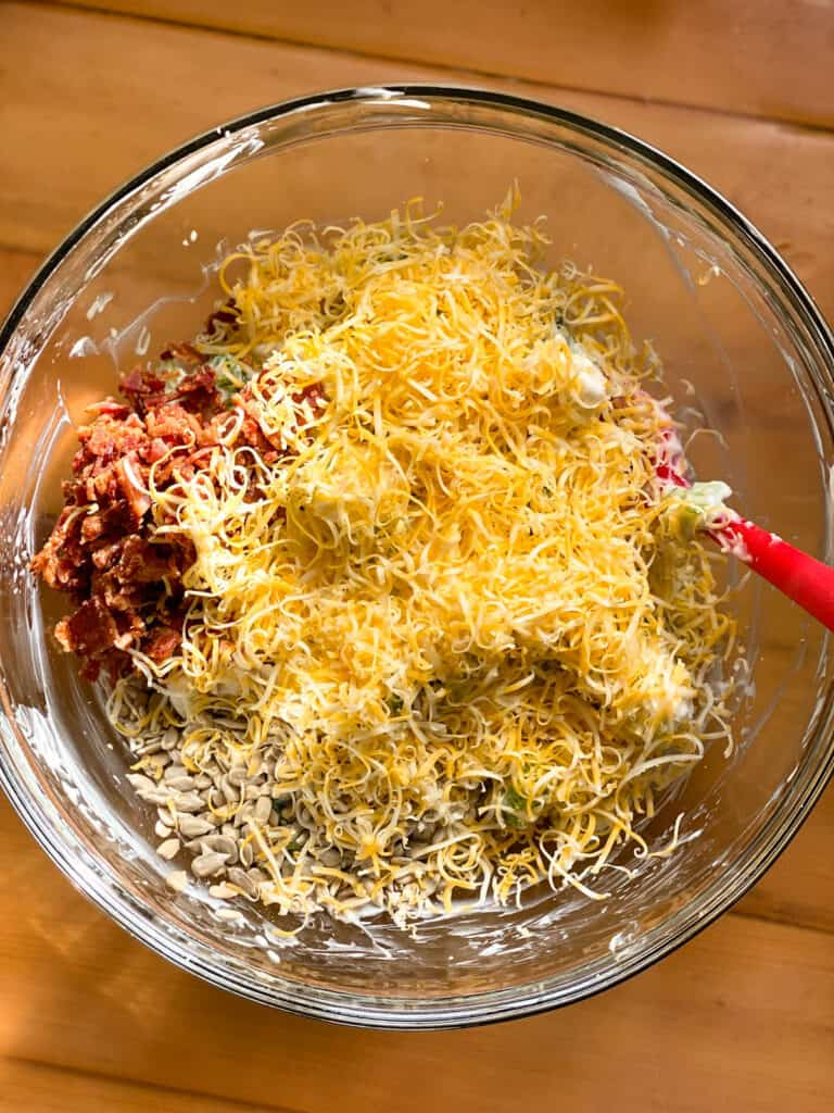 Last step in making salad, adding crumbled bacon, shredded cheese and sunflower seeds.