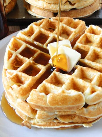 Homemade belgian waffles stacked on white round plate with pats of butter and getting a drizzle of maple syrup.