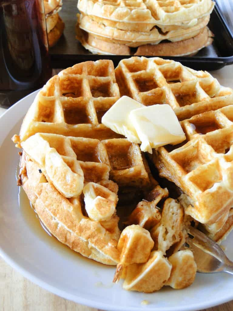 Stack of homemade belgian waffles on white round plate with a portion cut and on fork.