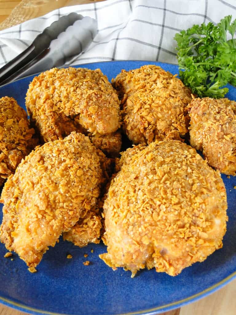 Close view of crispy corn flake chicken on round blue plate with tongs for serving.