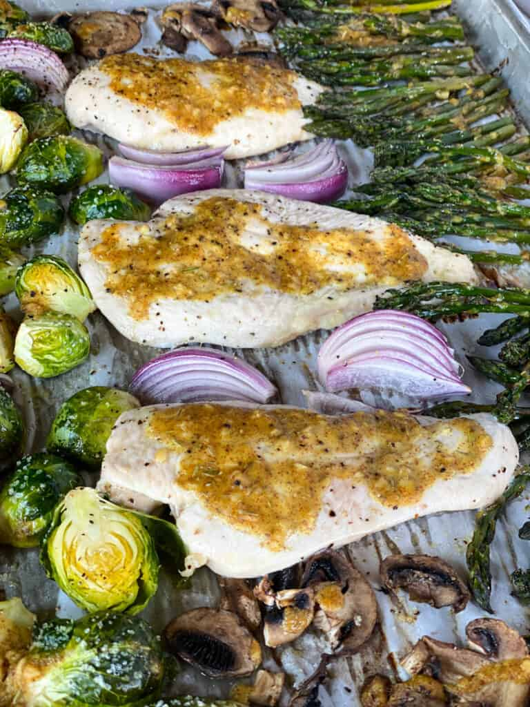 Top view of honey mustard chicken and vegetables cooked on sheet pan.