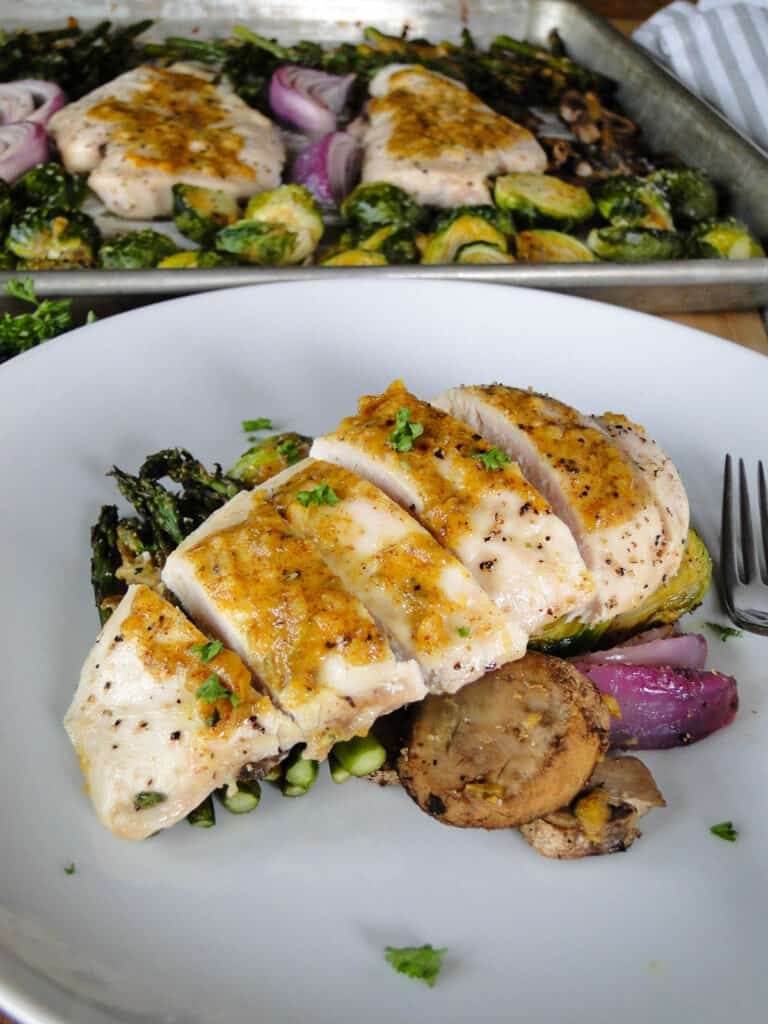 Sheet pan honey mustard chicken and vegetables served on white round plate with fork.