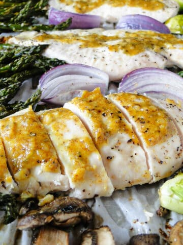 Close up of sheet pan honey mustard chicken and vegetables with spatula under sliced chicken breast.