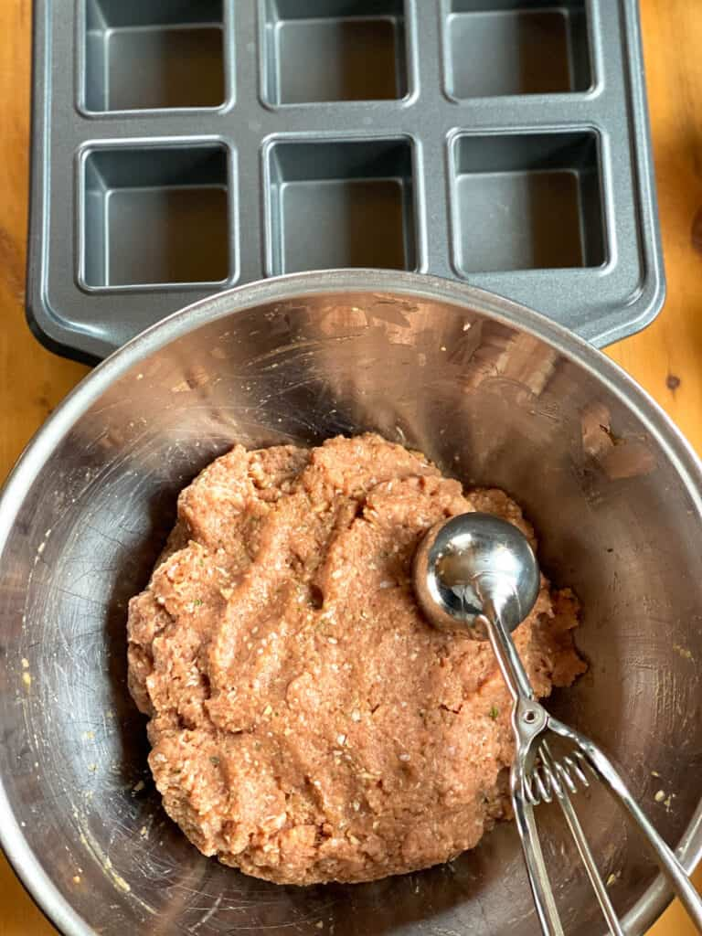 Meatloaf mixed in bowl with scooper ready to be put into brownie pan.