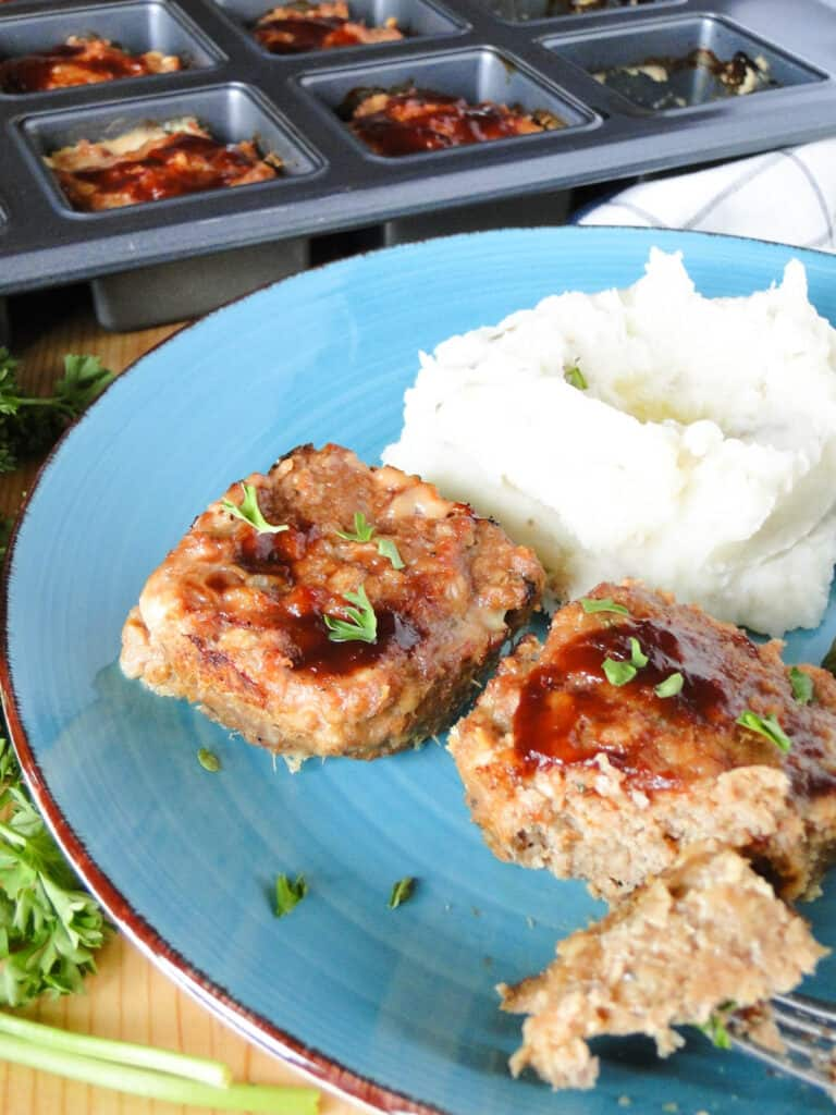 Mini bbq turkey meatloaves and mashed potatoes on blue plate with bite of meatloaf on fork.