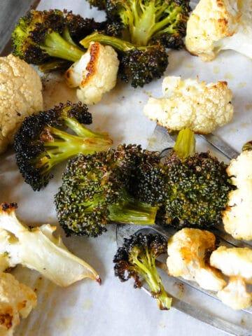 Roasted broccoli and cauliflower on sheet pan with spatula.