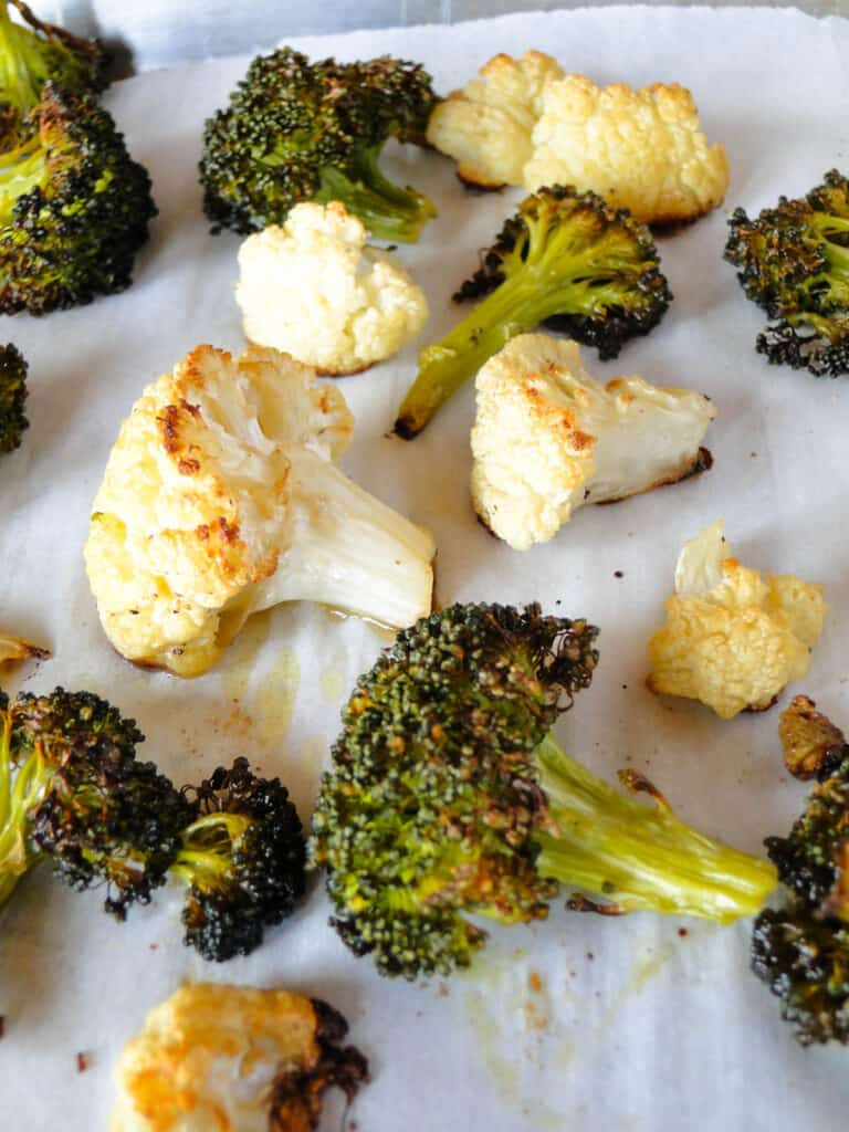 Close up view of crispy roasted broccoli and cauliflower on sheet pan.
