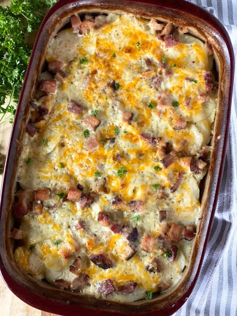 Top view of scalloped potatoes and ham in casserole dish.