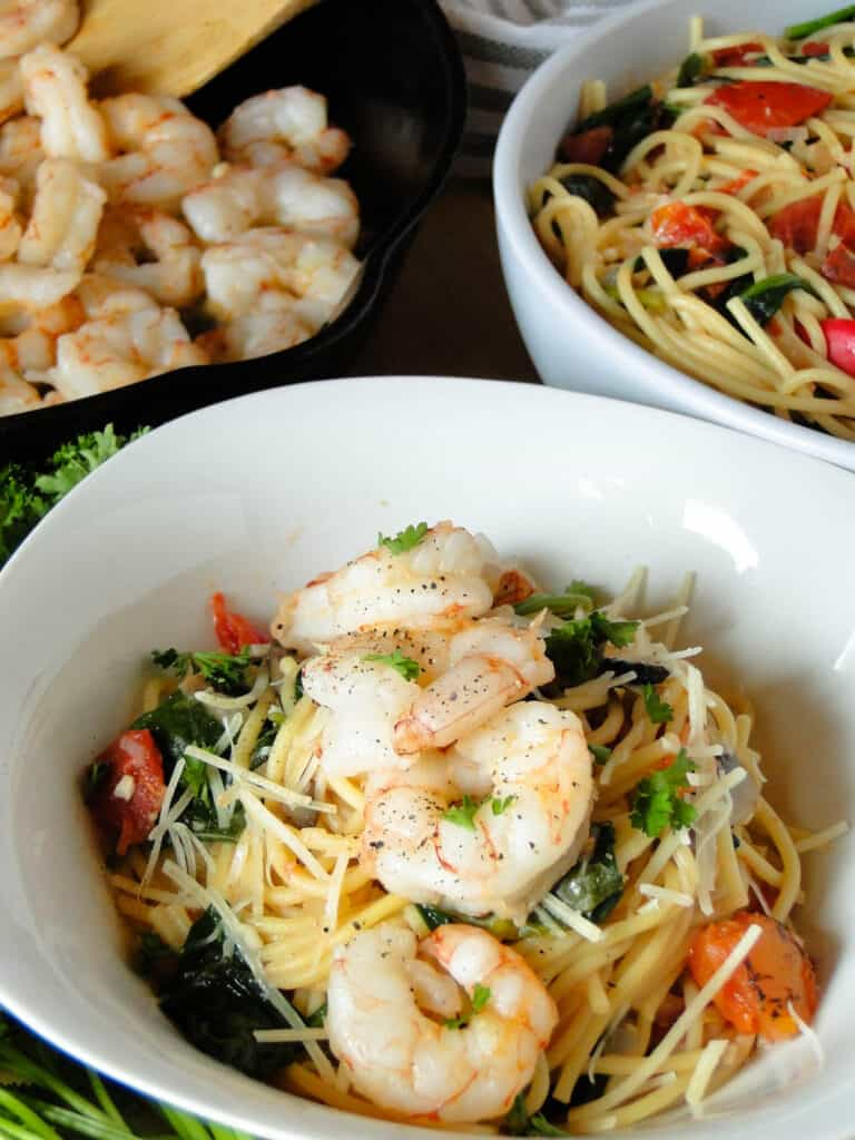 Easy spaghetti shrimp in white bowl in front of bowl of pasta and pan of shrimp.