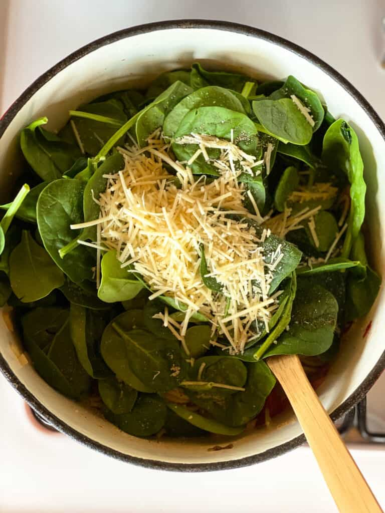 Spaghetti topped with spinach and shredded parmesan cheese.